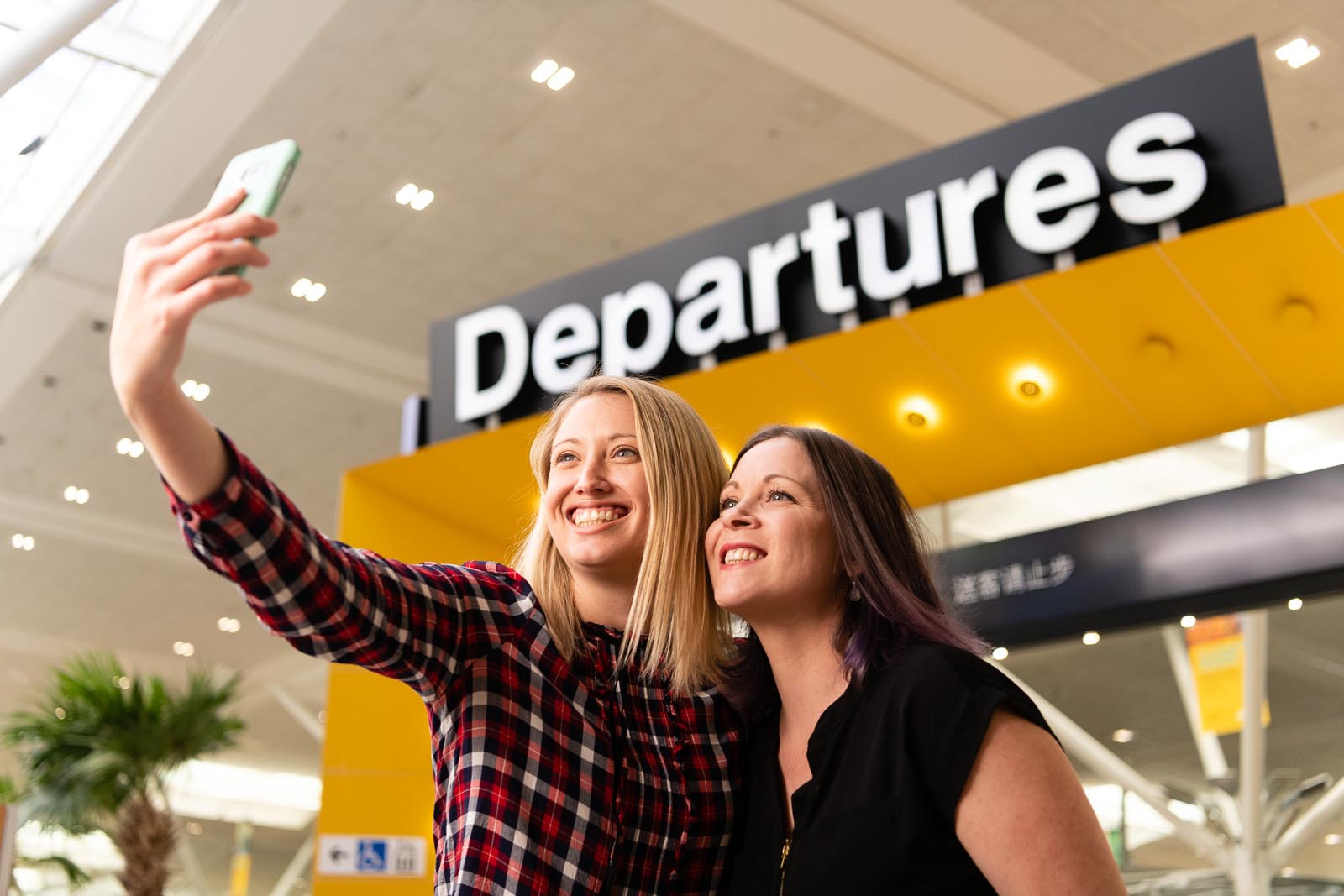 Two girls take a selfie at the BNE Airport Departures gate | Top tips for travelling in a large group while keeping friendships intact