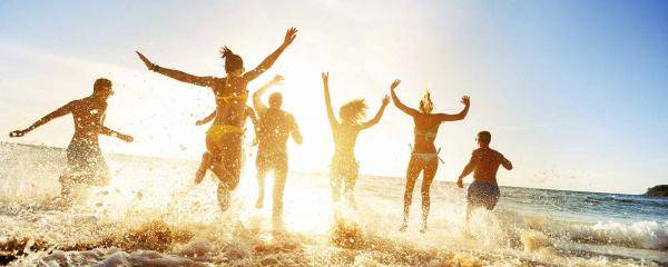Group of friends running into the ocean | Top tips for travelling in a large group while keeping friendships intact